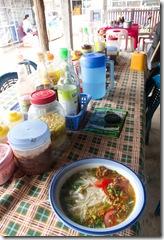 Une soupe de noodles pour le dejeuner (1euros) sur un marché, avec un remarquable choix de sauces.